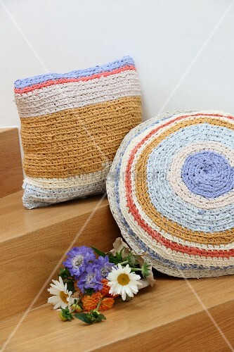 Flowers next to pastel cushions with crocheted covers made from T-shirt yarn