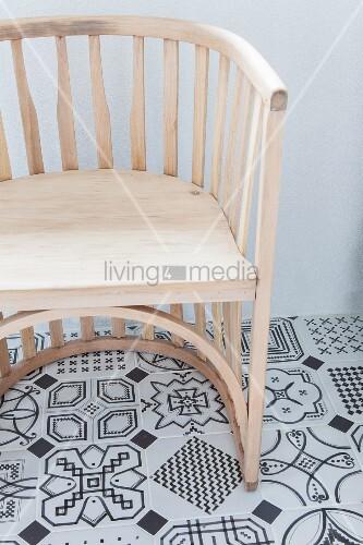 Halbrunder Holzstuhl auf schwarz-weiß gemustertem Fliesenboden