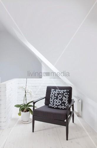 Schwarzer Sessel mit gemustertem Kissen unter der Dachschräge