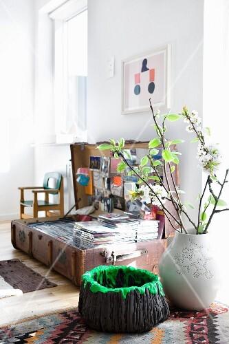 Lavaschale und Vase mit Zweigen vor einem Koffer mit CD-Sammlung