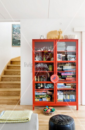 Games, glasses and magazines in red, glass-fronted cabinet next to foot of staircase