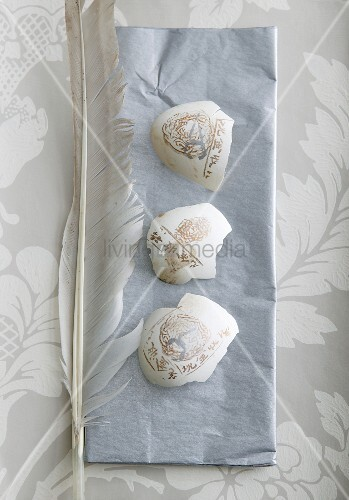 Decorated pieces of egg shell and feathers on grey napkin