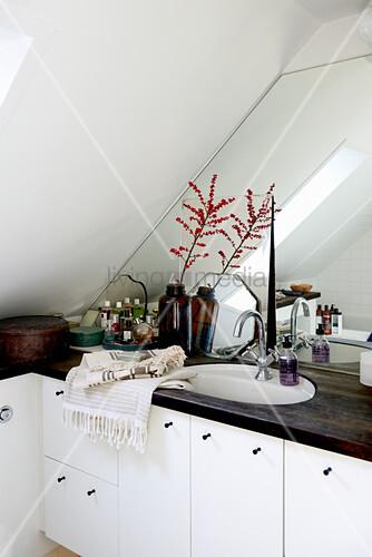 Vintage-Deko im Bad unter der Dachschräge mit verspiegelter Wand ...