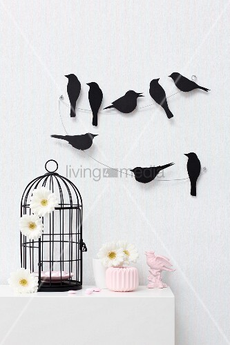 Bird silhouettes sitting on a wire mounted on wall