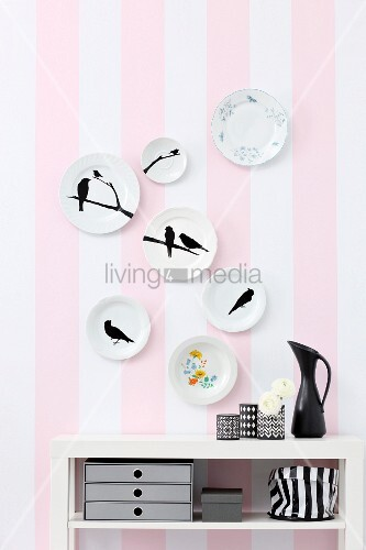 Decorative wall plate painted with bird silhouette on striped wallpaper
