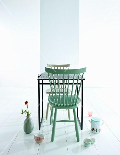 Mintgrüner Holzstuhl an schwarzem Tisch und Geschirr mit Retro Flair auf weißem Boden arrrangiert