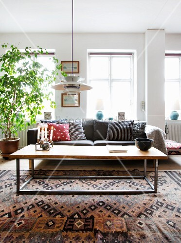 Coffee table with metal frame on woven rug in front of sofa