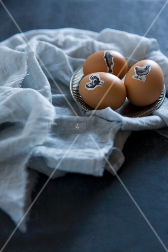 Easter eggs decorated with animal stickers on pewter saucer and fabrics