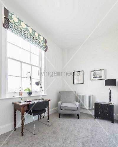 Arbeitszimmer mit grauem Teppichboden, Armlehnsessel und antikem Schreibtisch