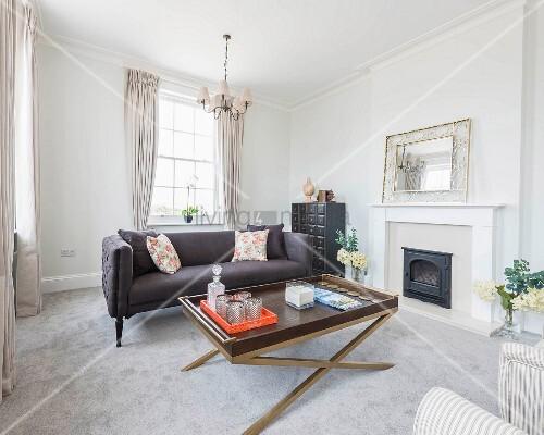 Eleganter Wohnbereich mit Polstercouch und Couchtisch vor Gaskamin