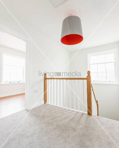 An empty staircase with grey carpet and a wooden railing, with an orange lampshade above