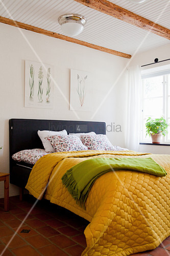 Yellow quilted bedspread on bed in rustic bedroom