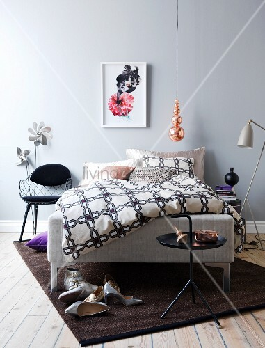 Copper pendant light and brown rug in grey bedroom