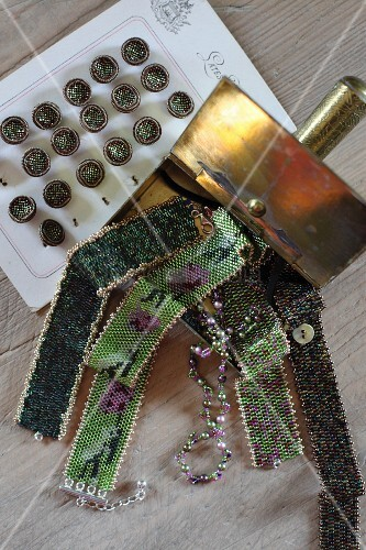 Various glass-bead chokers in tin next to vintage buttons