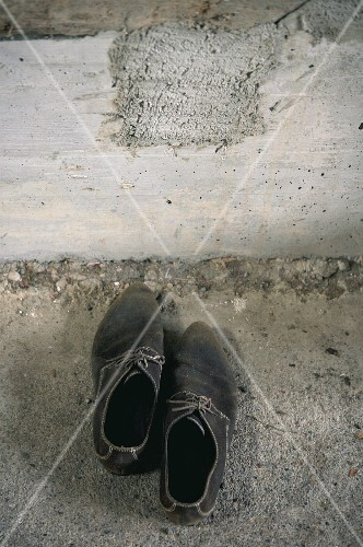 Pair of worn men's shoes next to concrete wall