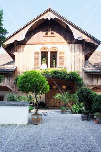 Kübelpflanzen auf dem Hof mit Kiesbett vor einem altem Holzhaus