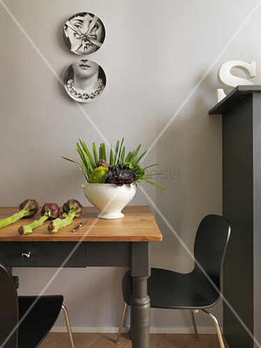 Decorative wall plates above vegetables on wooden table and designer chairs