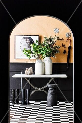 Keramikvasen mit Blätterzweigen und Sumba-Satuten auf Konsolentisch, davor schwarze Stiefel auf schwarz-weißem Fliesenboden