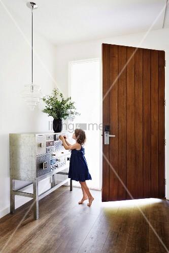 Mädchen an Konsole in Schmuckkästchen-Look im Flur, geöffnete Eingangstür