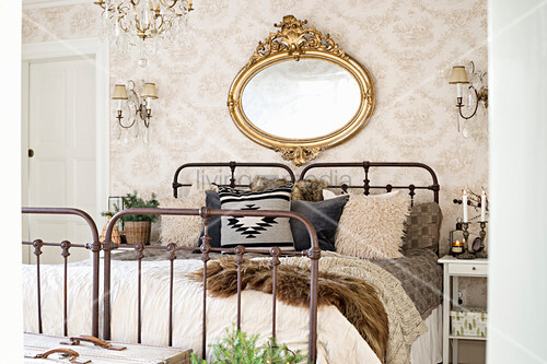 Oval, gilt-framed mirror above vintage metal bed