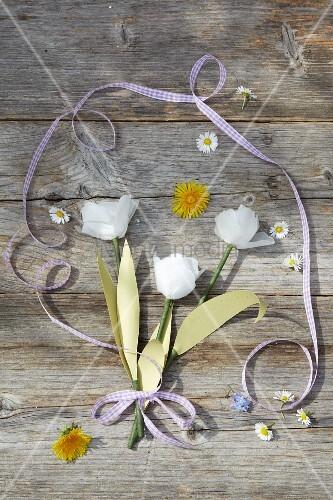 Gebastelte Tulpen aus Papier mit Blüten auf Holzbrettern