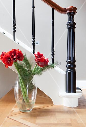 Strauß mit roten Amaryllis in der Glasvase vor dem Treppengeländer