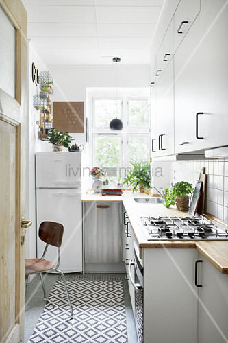 Simple white fitted furnishing in narrow kitchen