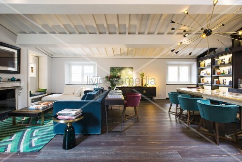 Blue sofa, fireplace, long table, shell chairs and white wood-beamed ceiling in open-plan interior