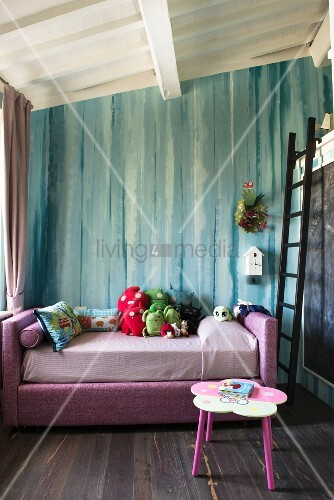 Soft toys on pink bed in front of turquoise wall in girl's bedroom with ladder leading to loft level on one side
