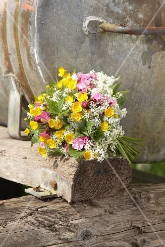 Wiesenblumenstrauss aus gelbem Hahnenfuss, rosa Kuckucksblumen und weissem Wiesenkerbel