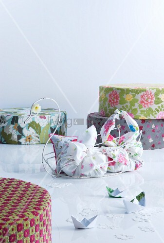 Colourful pouffes and fabric bags in metal swan-shaped basket
