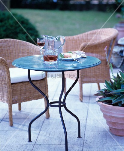 Glass jug on round garden table and wicker chairs on terrace