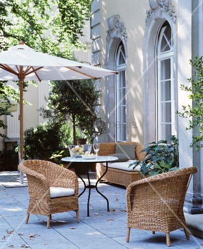 Wicker furniture and parasol on courtyard terrace of town villa