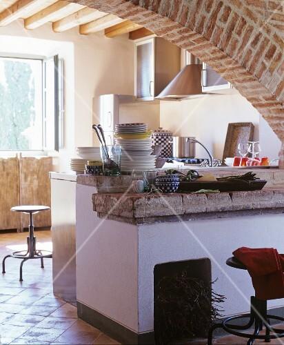 Rustikale Küche mit Segmentbogen und Ablage aus Naturstein