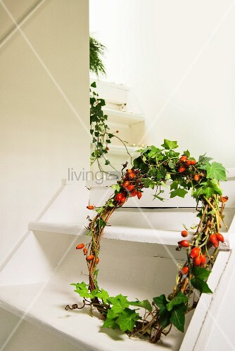 Hand-made wreath of rose hips and ivy tendrils on white wooden staircase