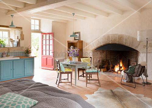 Kamin mit brennendem Feuer in offenem Wohnraum mit Küchentisch und Doppelbett