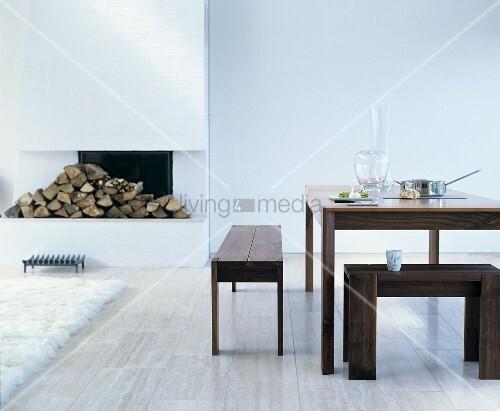 Essbereich mit Holzmöbeln vor offenem, weißem Kamin