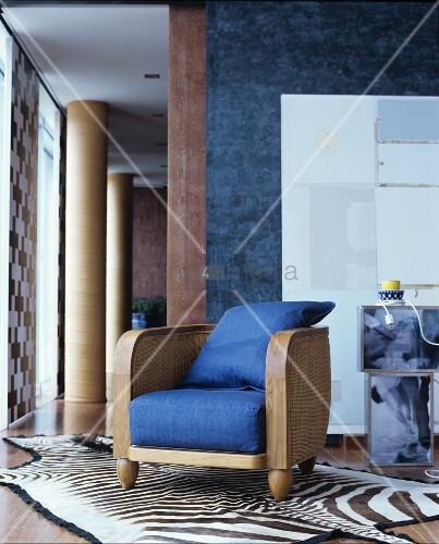 Rattan and wood lounge chair with blue cushions on zebra-skin rug