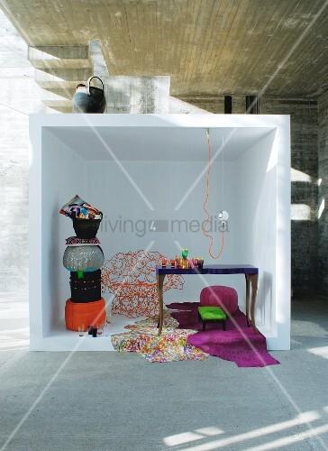 Gestapelte Sitzpoufs in weißem Kubus vor Betonwand