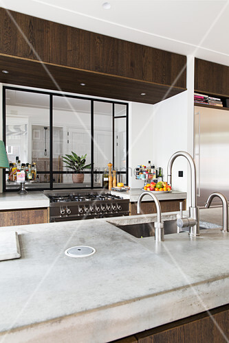 View across island counter with concrete worksurface and through interior window