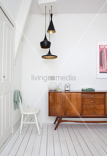 Old sideboard in hallway with white wooden floor