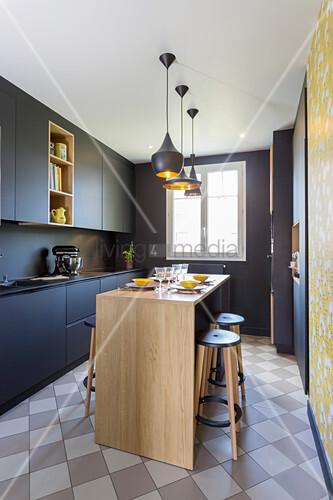 Black designer kitchen with central dining area