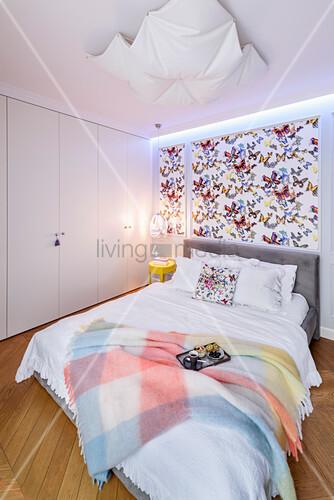 Schmetterling-Tapete überm Bett im Schlafzimmer mit Schrankwand