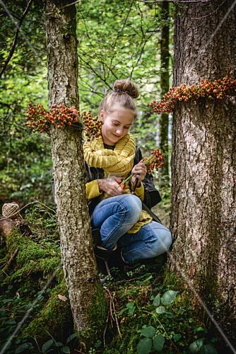 Mädchen im Wald mit Kränzen aus Hagebutte