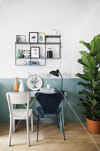 Small desk and chairs below shelves on two-tone wall