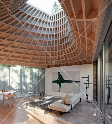 Minimalist living room in modern extension with glass walls and funnel-shaped roof