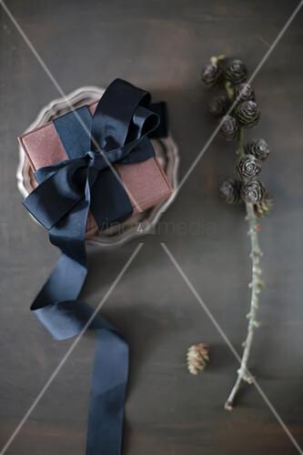 Verpacktes Geschenk mit schwarzem Dekoband auf Zinnteller