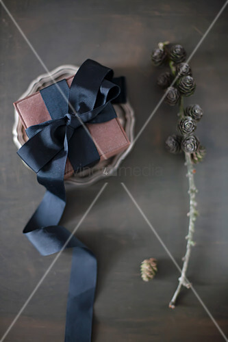 Wrapped gift decorated with black ribbon on pewter plate