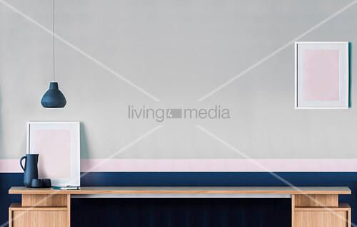 Langer Schreibtisch vor grau-blauer Wand mit rosa Streifen