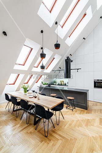 Kücheninsel mit Barhockern und Esstisch mit schwarzen Stühlen in hohem Raum mit Dachschräge